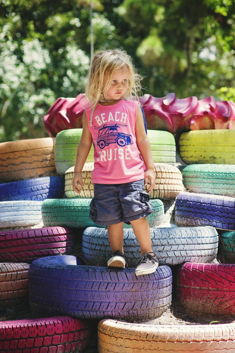 toddler standing on colorful piles