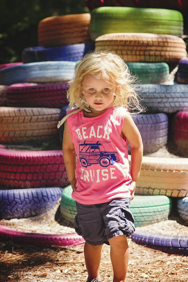 toddler standing in front of a pile of colorful tires