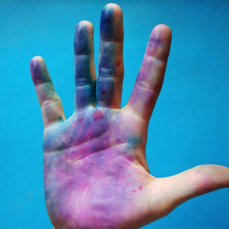 hand covered in pink and purple paint on a blue background