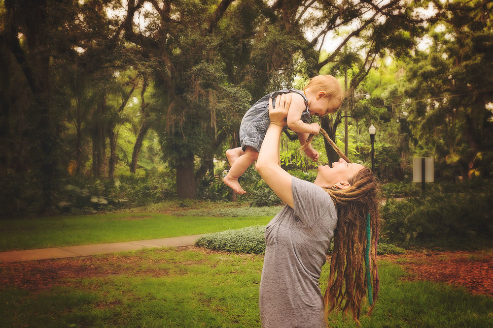 mother holding up a baby in a park