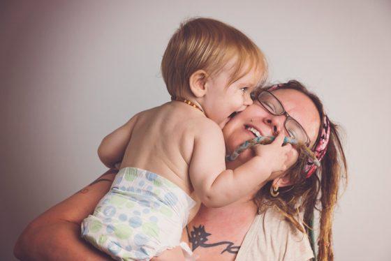 image of motherhood- a baby giving mom sloppy kisses on the cheek