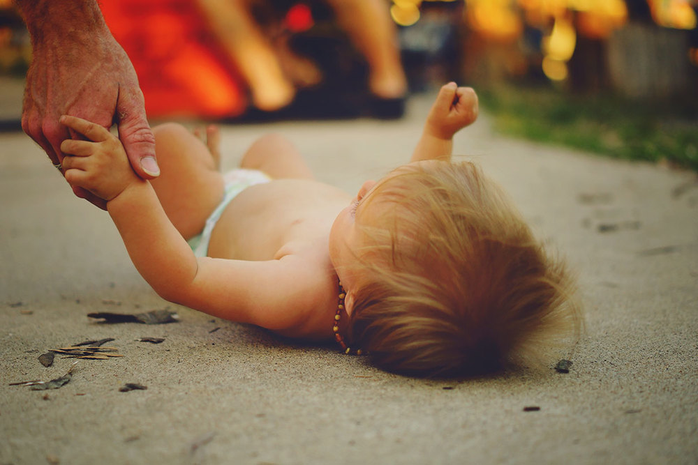 Toddler boy laying on the ground