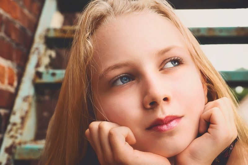 Blonde tween girl with posed on a stairwell