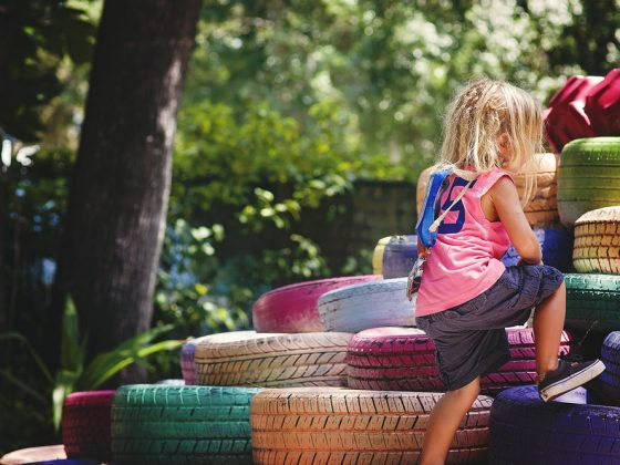 toddler climbing a colorful pile of tires