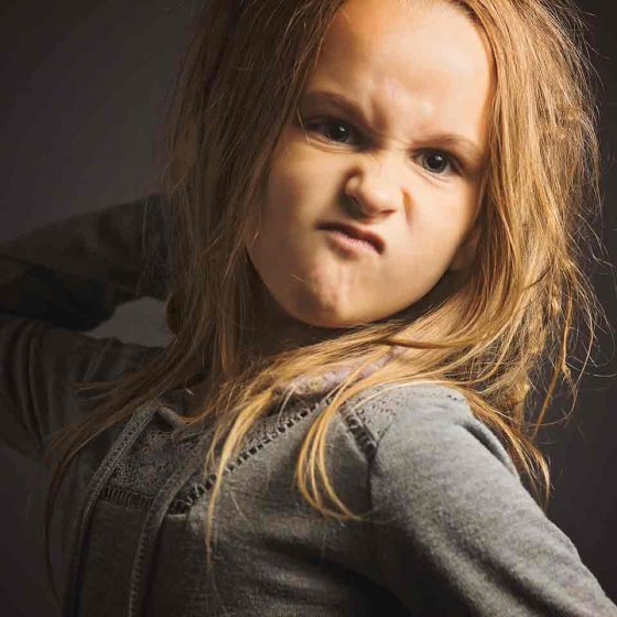 Young girl on dark background making a mad face