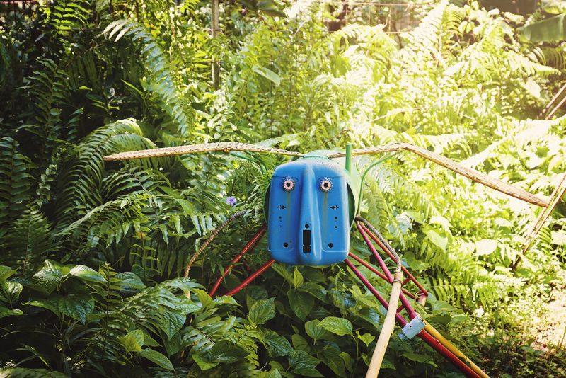 metal sculpture of a bug in a garden