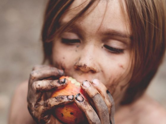 dirt covered kid eating apple
