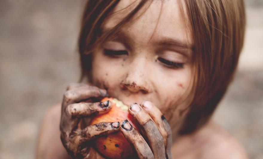 dirt covered kid eating apple